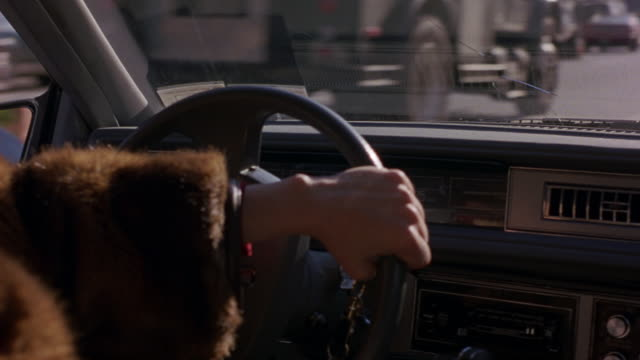 CLOSE ANGLE HAND HELD OF WOMAN DRIVER IN FUR COAT. POV FROM BACK SEAT OF 1972 CADILLAC SEDAN DEVILLE THROUGH FRONT WINDSHIELD. SEE ARMS OF WOMAN DRIVING CAR.