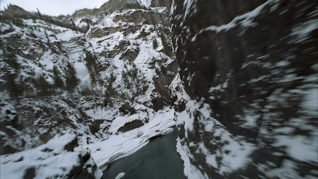 aerial of forward window pov from helicopter or airplane flying through mountain gorge in winter. see partially frozen river with ice and open water. - canyon stock videos & royalty-free footage