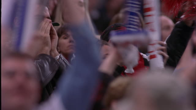 medium angle of men watching game with binoculars within crowd in stadium. see people cheering, standing up, blowing horns, clapping, and yelling. - binoculars stock videos & royalty-free footage