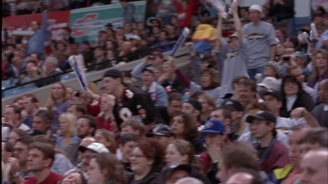 pan right to left of crowd in stadium seats. see people cheering, clapping, and walking in aisles. could be small reaction to play or scoring. could be football, baseball, basketball, or hockey game in sports arena. - winter sport stock videos and b-roll footage