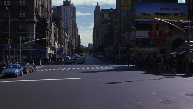 medium angle of new york city street intersection. see traffic light turn green and cars begin to move towards camera. see white 1987 buick lesabre turn left to cut off oncoming traffic and exit speeding to bottom. - 1981 stock-videos und b-roll-filmmaterial