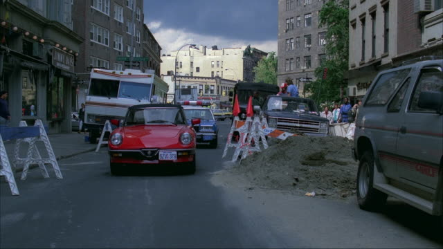 straight back process plate of street. start in alley facing front of red convertible and police car behind it. pulls back, turns left onto alley, parked cars and buildings on sides. - 1989 stock videos and b-roll footage