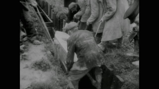 massive funeral service is held at the site of a mass grave for the dead of the devastating coventry bombing raid - コベントリー点の映像素材/bロール