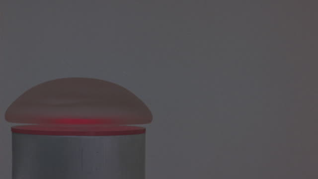CLOSE ANGLE OF SILVER CYLINDER WITH ROUNDED SILVER BUTTON ON TOP IN FRONT OF WHITE BACKGROUND. SEE RED LIGHT ON BOTTOM OF BUTTON. S