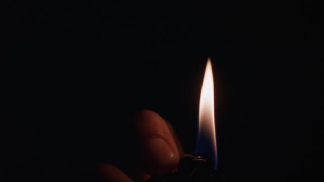 MEDIUM ANGLE OF HAND IGNITING CIGARETTE LIGHTER IN PITCH DARKNESS. SEE FLAME LIGHT UP PART OF HAND AS IT MOVES BACK AND FORTH IN POV. FIRES.