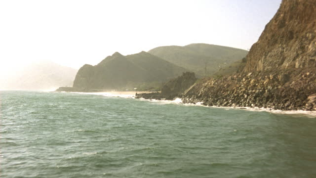 STEADICAM OF FLYING ALONE SHORELINE OF OCEAN AND ROCKY CLIFF. SEE CLIFFS ON RIGHT AS WAVES CRASH INTO LAND. SEE BEACH WITH GREEN LEAFY TREES ON HILL NEXT TO CLIFF.
