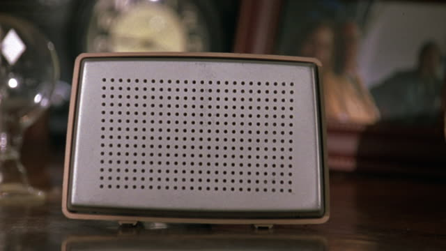 close angle of silver intercom speaker sitting on brown wooden desk in home office. zoom out to see wooden chair and shelves full of books next to desk. see lamp and telephone and clock on desk. - intercom stock videos and b-roll footage