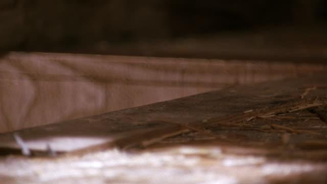 medium angle of worn down wooden floor with hay on it. see square opening to left of floor. see part of short stone wall in background. neg cut. - 2000 2010 stil bildbanksvideor och videomaterial från bakom kulisserna