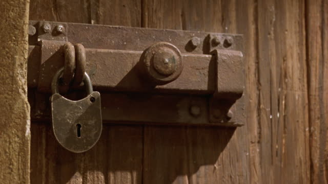 medium angle of wood paneled door with vintage medieval style metal lock and latch. see dagger swing from right of pov and knock open lock. see open lock hanging on latch of door. shot in 40 fps slow motion. - 2000 2010 stil bildbanksvideor och videomaterial från bakom kulisserna