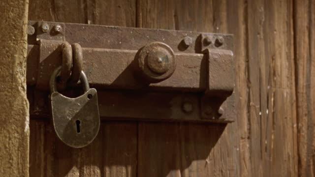 medium angle of wood paneled door with vintage medieval style metal lock and latch. shot in 40 fps slow motion. neg cut. - 2000 2010 stil bildbanksvideor och videomaterial från bakom kulisserna