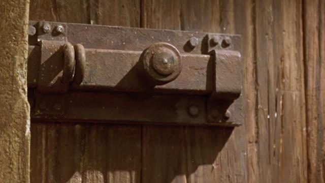 medium angle of brown wood paneled door with vintage medieval style metal latch. see light shining on door from out of pov. shot in 40 fps slow motion. - 2000 2010 stil bildbanksvideor och videomaterial från bakom kulisserna