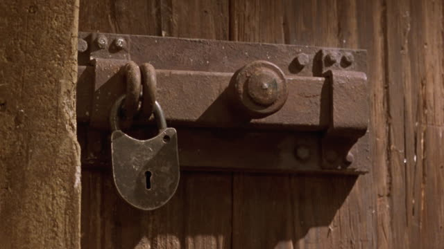 medium angle of brown wood paneled door with vintage medieval style metal lock and latch on it. see dagger swing in from right and strike lock. see lock fly off of latch. - dagger stock videos & royalty-free footage