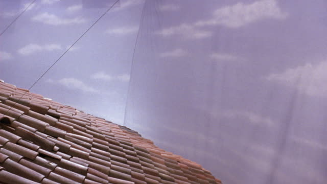 MEDIUM ANGLE OF SPANISH STYLE RED TILE ROOF. SEE LEFT SIDE OF ROOF BEGIN TO EXPLODE.  SEE BLACK WIRE EXTENDING OUT OF THE ROOF. SEE BLUE SKY IN BACKGROUND AND BLACK VERTICAL NET TO RIGHT OF ROOF. SHOT IN 60 FPS SLOW MOTION. EXPLOSIONS.