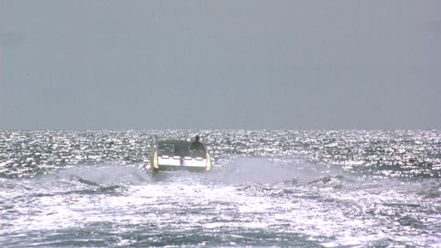 medium angle of back of white speed boat with red stripe and gold top. see boat move over waves in the ocean and create wake behind it. zoom in on boat and see blonde woman in gold bikini driving boat. pass boat and pan down on blue ocean water. - bikini top stock videos & royalty-free footage