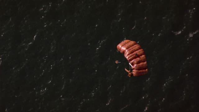 vidéos et rushes de aerial of man in brown jumpsuit falling to ocean. see person release brown parachute. see parachute open and track person as he floats down towards to water. - parachute