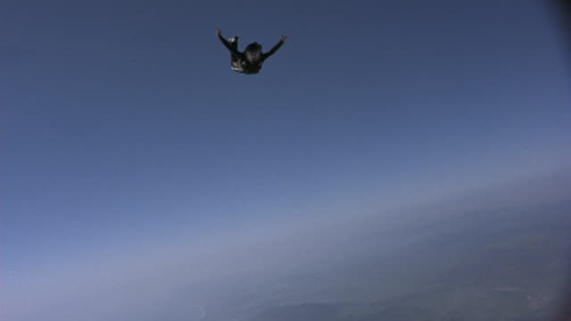 AERIAL OF PERSON IN TIGHT BLACK SKYDIVING SUIT JUMPING OUT OF RED HELICOPTER AND FALLING THROUGH THE AIR. SEE PERSON WEARING BLACK HELMET. SEE SHORELINE AND LAND BELOW AS SKYDIVER ZOOMS BACK AND FORTH THROUGH THE AIR.