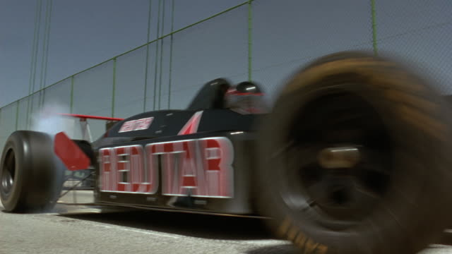 """MEDIUM ANGLE OF SIDE OF BLACK FORMULA ONE RACE CAR WITH RED STAR ON FRONT AND TEXT ON SIDE READING """"REDSTAR"""" ON GREEN SUSPENSION BRIDGE. SEE SMOKE RISE FROM TIRES AS RACE CAR PEELS OUT TO RIGHT AND EXITS POV. SHOT IN 18 FPS."""