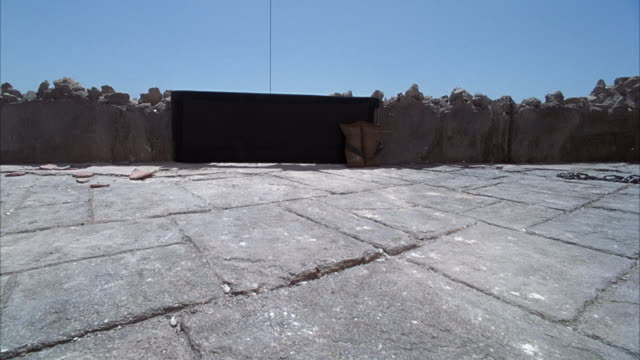 MEDIUM ANGLE OF FLAT STONE AREA SURROUNDED BY STONE WALL. SEE POSSIBLE IRON GATE BLOCKING PORTION OF WALL. SEE ROPE EXTENDING FROM TOP OF GATE TO TOP OF FRAME.  SEE OCEAN AND ISLAND IN BACKGROUND. SEE CLEAR BLUE SKY. SEE CAMERA SHIFT UP.