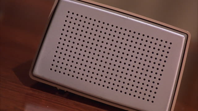 close angle of white and beige intercom speaker sitting on wooden desk. pov tilted at angle. see person walk in background. - intercom stock videos and b-roll footage
