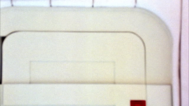 MEDIUM ANGLE OF WHITE WALL OR ROOM SEE POSSIBLE DOOR IN BACKGROUND. COULD BE INTERIOR OF SPACE SHIP. CAMERA OUT OF FOCUS.