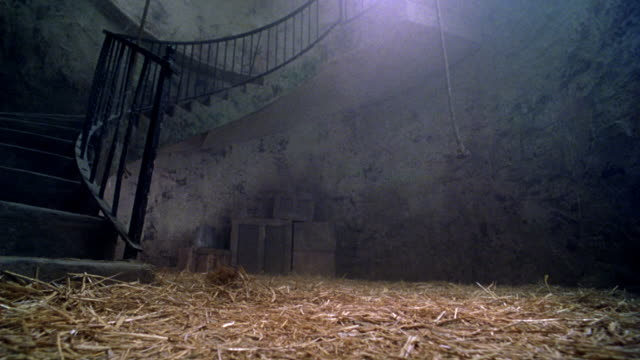 medium angle of staircase at bottom of tower. see straw on ground, boxes in background, two ropes hanging through middle of frame. - falls church stock videos & royalty-free footage