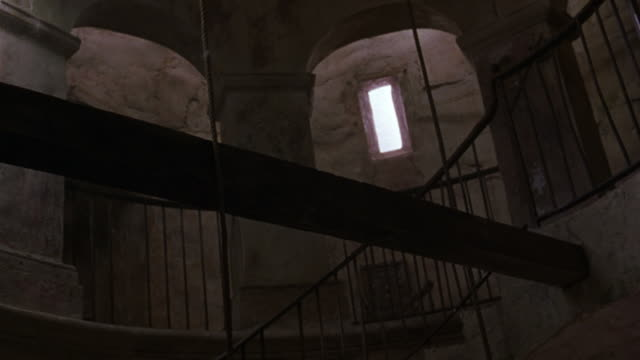 medium angle, interior of stone bell tower. see walkway and staircase with metal railings, small rectangular window, three archways, three columns and one large wooden beam running across  interior of tower. - bell tower tower stock videos and b-roll footage
