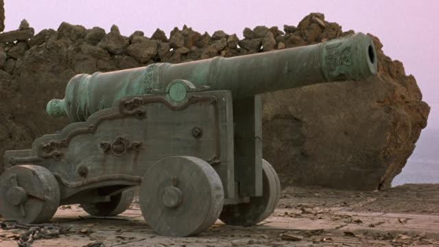 medium angle establish of antique cannon. see cannon on dirt, facing frame right. see large rock wall in background. - 2000 2010 stil bildbanksvideor och videomaterial från bakom kulisserna