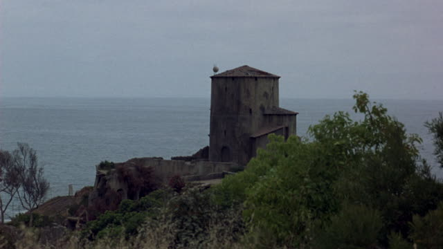 medium angle of stone or concrete tower on edge of sea cliff. see wall and trees surrounding tower. see ocean in background. see tower explode. see balls of fire engulf tower. see black smoke rise. see ruins of tower as smoke clears. explosions. - explosion wall stock videos and b-roll footage