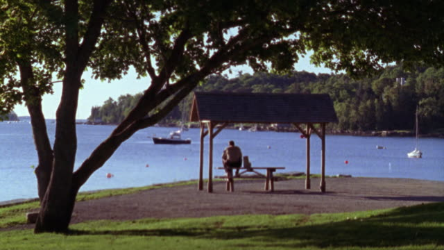 wide angle of man sitting on picnic table overlooking river or lake. boats visible in water. - picnic table stock videos & royalty-free footage