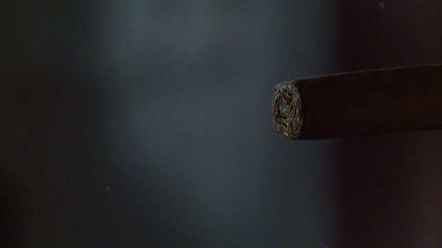 close angle of cigar and cigarette lighter. thumb flicks lighter and lights cigar. smoke. - sigaro video stock e b–roll
