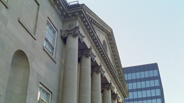 UP ANGLE OF IONIC COLUMNS ON FACADE OF BANK, GOVERNMENT BUILDING, OR LIBRARY. TRIANGULAR PEDIMENT VISIBLE. GREEK OR CLASSICAL ARCHITECTURE. MODERN GLASS OFFICE BUILDING IN BG.