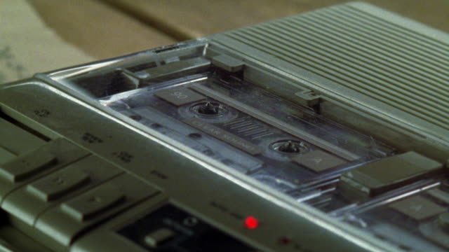 close angle of a tape recorder or audio cassette player, probably used for wiretapping or surveillance. - 盗聴点の映像素材/bロール