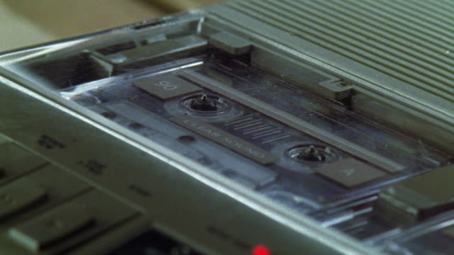 zoom in on a tape recorder or audio cassette player, probably used for wiretapping or surveillance. - 盗聴点の映像素材/bロール