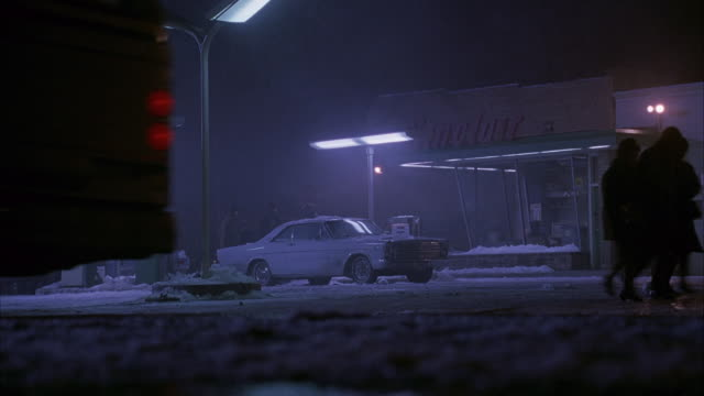 """wide angle of gas station at night during snow. see light snow falling on ground. two people walk by camera. see white vintage car parked by gas pump. men standing outside of car chatting. see """"sinclair"""" written on top of gas station . - tankstelle stock-videos und b-roll-filmmaterial"""