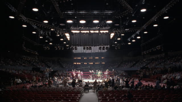 wide angle of crowd cheering on boxing match in middle of boxing ring. large arena. see opposing boxers at each side of ring, warming up for match. action. - boxing ring stock videos & royalty-free footage