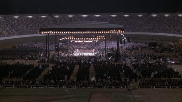 WIDE ANGLE OF BOXING RING IN MIDDLE OF OUTDOOR SPORTS ARENA. SEE SPECTATORS PACKED INTO STADIUM. FRONT ROW SPECTATORS STAND AND APPLAUSE MULTIPLE TIMES. ACTION. CROWDS.