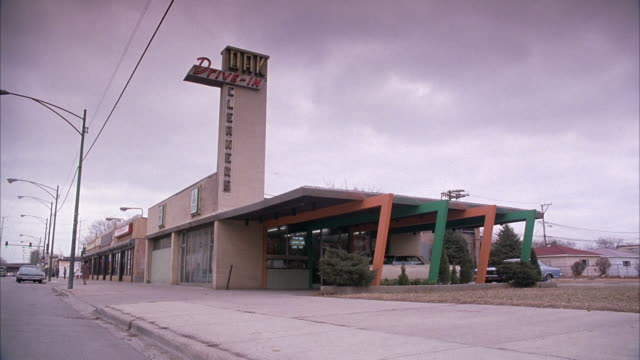 wide up angle of drive-in restaurant. see white car pull out of driveway and drive down street away from pov. see pedestrians walking on sidewalk dressed in 1960's attire. overcast sky. - 1970年点の映像素材/bロール