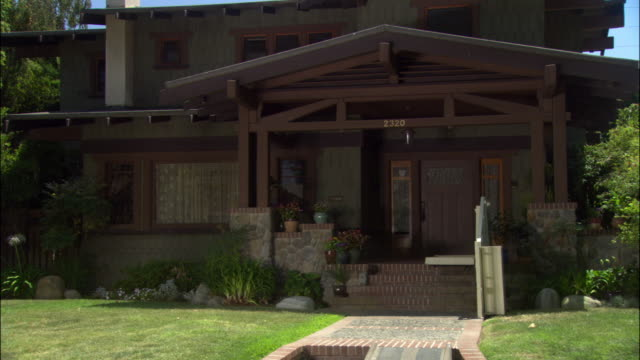 wide angle of front entrance to craftsman style bungalow.  house has shingle siding, exposed wood beams and wide eaves. two story house, middle class or upper class. - bungalow stock videos and b-roll footage