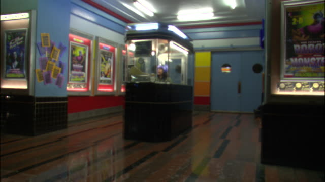 medium angle of movie theatre entrance. see woman wearing purple helmet sitting in ticket booth. see movie posters flanking entrance at either side. see poster advertising robot monster at right. see glossy tile floor reflecting lights at top. - booth stock videos & royalty-free footage