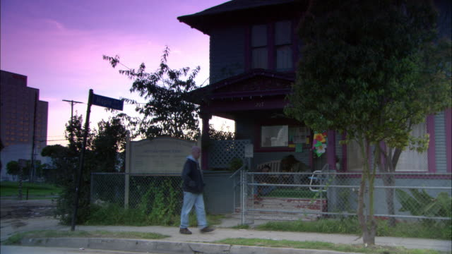 medium angle of teal and purple painted two story middle class community center on corner of street. see four foot chain link fence bordering house. - 連続するイメージ点の映像素材/bロール