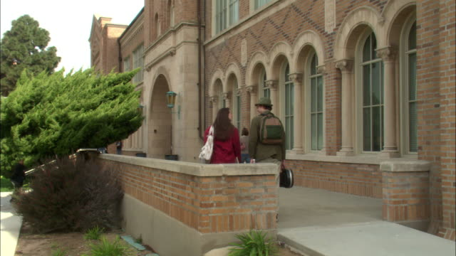 medium angle of a female student wearing red jacket carrying white bag walking away from pov with male student in olive green coat and hat carrying a guitar case on walkway on left of red brick school with arched windows and short brick wall. - 連続するイメージ点の映像素材/bロール