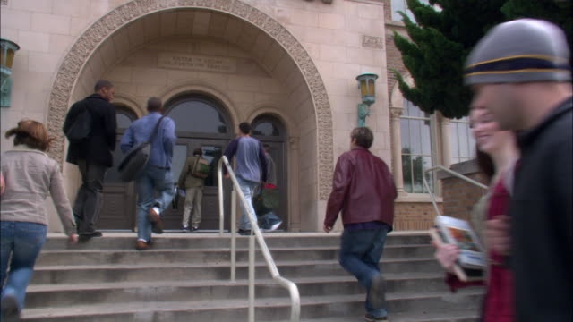 MEDIUM ANGLE OF STUDENTS CARRYING BACKPACKS AND BAGS ENTERING OPEN BROWN DOOR TO TAN SCHOOL AT TOP OF STAIRS. SEE THREE WHITE RAILINGS GOING DOWN STAIRS.