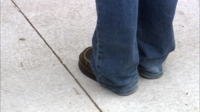 close angle down of female legs wearing long blue tight denim jeans and dark brown dress shoes standing on light concrete. track legs walking along concrete to dark concrete steps. - baggy jeans stock videos & royalty-free footage