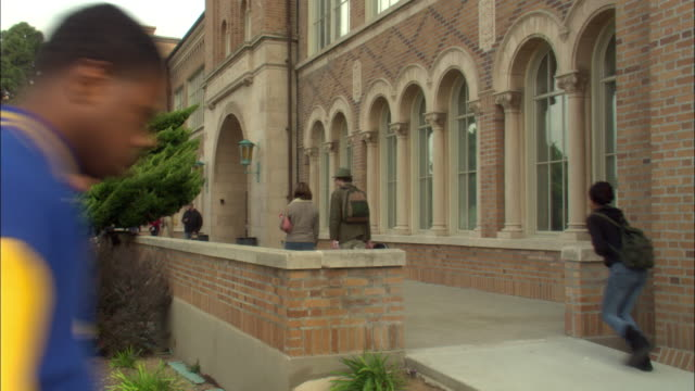 MEDIUM ANGLE OF A FEMALE STUDENT WEARING GREY JACKET CARRYING PINK PURSE WALKING AWAY FROM POV WITH MALE STUDENT IN OLIVE GREEN COAT AND HAT CARRYING A GUITAR CASE ON WALKWAY ON LEFT OF RED BRICK SCHOOL WITH ARCHED WINDOWS AND SHORT BRICK WALL.