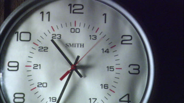insert close angle tracking shot of round white analog clock with silver frame and black hands hanging on wood paneled wall. see time on clock read ten thirty-five. - analog stock videos and b-roll footage
