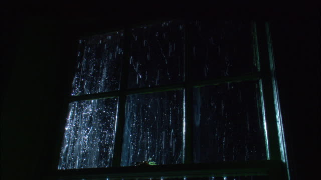 medium angle of six paneled glass window. see rain falling outside of window. see light appear outside left of window. - window frame stock videos and b-roll footage