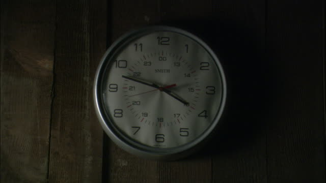 INSERT CLOSE ANGLE OF ROUND WHITE ANALOG CLOCK WITH SILVER FRAME AND BLACK HANDS HANGING ON WOOD PANELED WALL. SEE WORD SMITH IN BLACK TEXT ON CLOCK. SEE TIME ON CLOCK READ THREE FORTY-EIGHT. SEE DULL LIGHT FROM LEFT AND DARKER PANELS ON THE RIGHT.