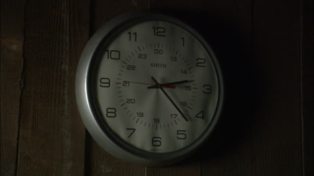 INSERT CLOSE ANGLE OF ROUND WHITE ANALOG CLOCK WITH SILVER FRAME AND BLACK HANDS HANGING ON WOOD PANELED WALL.