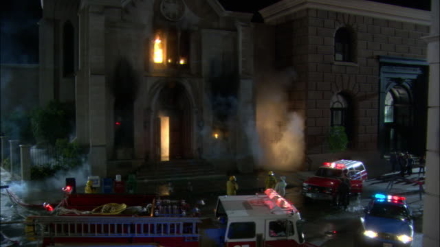 medium angle of grey stone three story synagogue with brown large brick two story building on right. see fire engine along with police car and fire suv with lights flashing. - fire hose stock videos & royalty-free footage