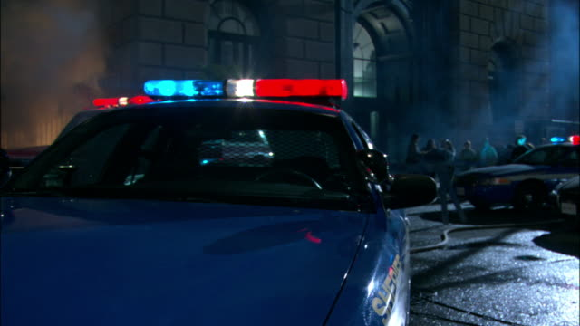 MEDIUM ANGLE OF PARKED ROYAL BLUE POLICE CAR WITH LIGHTS FLASHING IN FOREGROUND. SEE SMALL CROWD OF PEOPLE IN BACKGROUND IN FRONT OF GREY STONE MULTI STORIED BUILDING WITH ARCHED WINDOWS IN URBAN AREA. SEE POLICEMAN JOG TOWARDS POV AND OFF RIGHT.